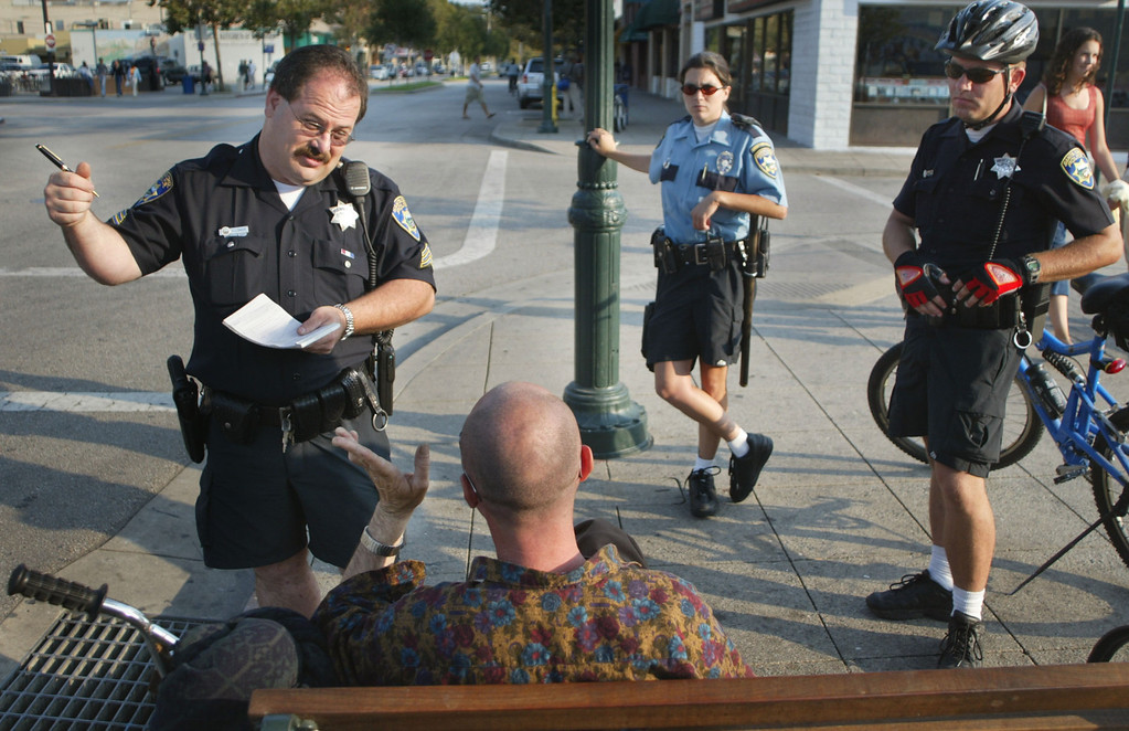 Description of . In this 2002 file photo, Santa Cruz police Sgt. Loran Baker, left, writes a traffic citation for a bicyclist who ran a stop sign on Pacific Avenue in Santa Cruz. Community Service Officer Kayla Gray and officer Derrick Phelps look on. (Patrick Tehan/Media News file)