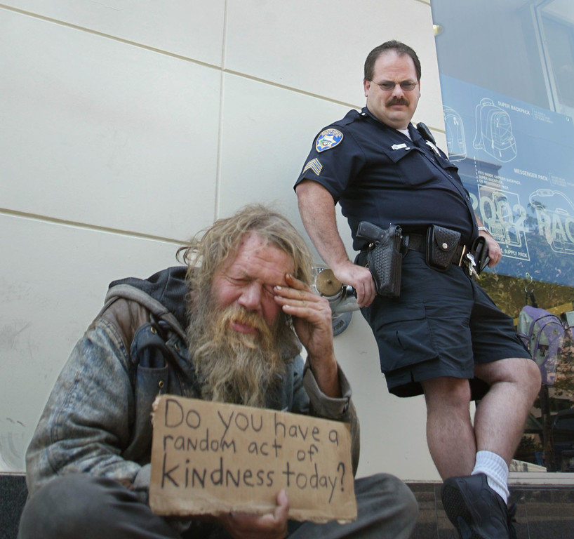 Description of . In this 2002 file photo, Santa Cruz Police Sgt. Loran Baker chats with regular panhandler Chuckie Jensen on Pacific Avenue in Santa Cruz. Baker subsequently asked him to move farther away from the GAP store he was sitting in front of. (Patrick Tehan/Media News file)