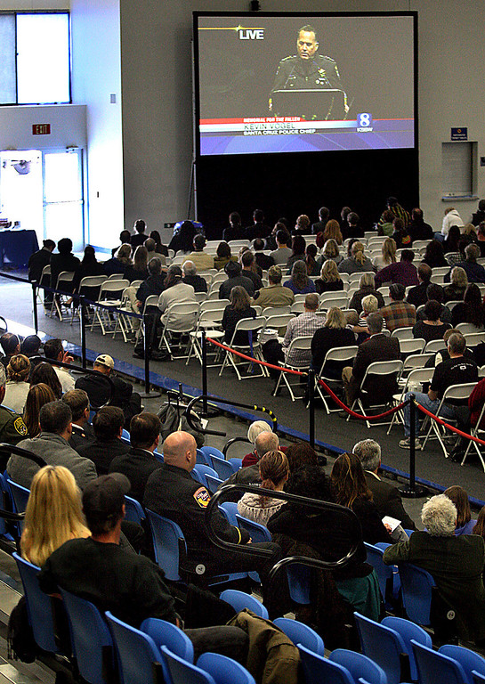 . Mourners in Kaiser Permanente Arena watch the live telecast of Santa Cruz Police Chief Kevin Vogel\'s eulogy of detective Sgt. Loran \'Butch\' Baker and detective Elizabeth Butler at HP Pavilion in San Jose Thursday.  (Dan coyro/Sentinel)