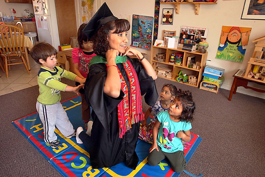 . Immigrant Elvia Morales learned English at Watsonville Adult School, went on to earn a master\'s degree studying nights and weekends after her days working in day care.  Her day care charges help her with the cap and gown she\'ll be wearing.  (Dan Coyro/Sentinel)