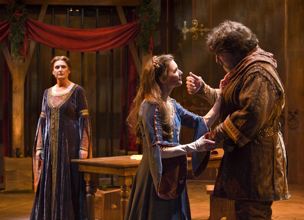 """. Eleanor of Aquitaine (Kandis Chappell) watches her husband, King Henry II (Marco Barricelli), and his mistress, Alais Capet (Mairin Lee) in the Shakespeare Santa Cruz production of \""""The Lion In Winter.\"""" (Photo courtesy of RR Jones)."""