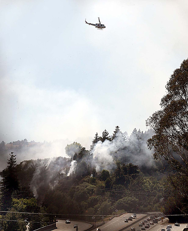 . A CalFire helicopter hovers over the smoke and fire near the Fishhook and behind the Elks Club Thursday afternoon.  (Dan Coyro/Sentinel)