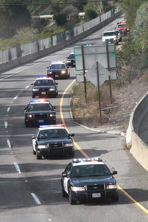 . Hundreds of police cars make their way  down Highway 17 through Los Gatos during a funeral procession for two slain Santa Cruz police officers as it makes its way to San Jose\'s HP Pavilion, and the funeral.