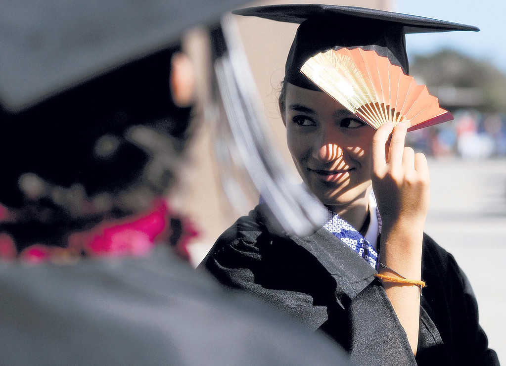 . Amelia Rupp shades her face from the sun using a Japanese fan while waiting for the Pacific Collegiate School commencement ceremony to begin Friday evening. (Matthew Hintz/Sentinel)