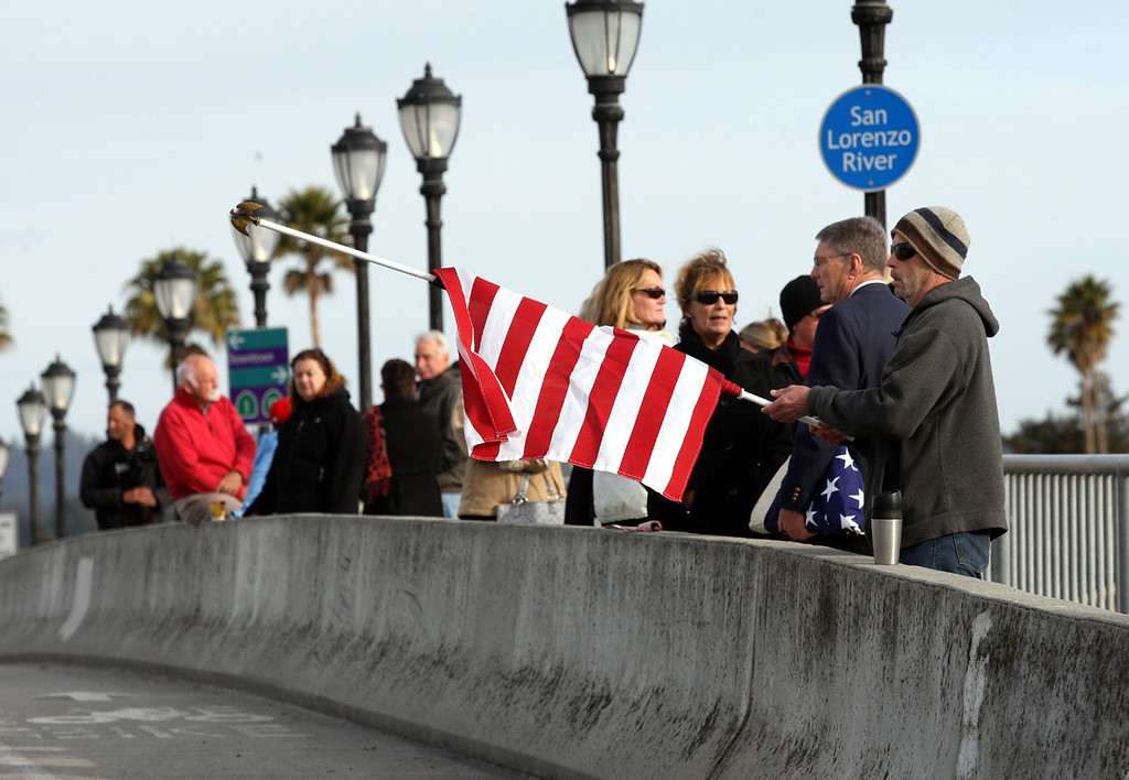 . Hank Springer unfurls his flag on the Riverside Bridge Thursday as he waits with other Santa Cruz residents for the funeral procession of slain Santa Cruz Police detectives Sgt. Loran \'Butch\' Baker and Elizabeth Butler.  (Dan Coyro/Sentinel)