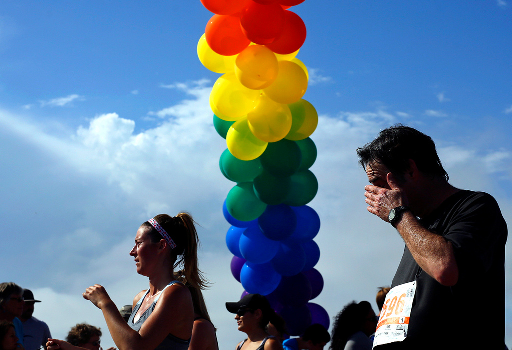 . A runner wipes the sweat from his eyes as he crosses underneath a rainbow-colored balloon archway in Capitola Village on Sunday morning at the end of the Wharf to Wharf race. (Kevin Johnson -- Santa Cruz Sentinel)