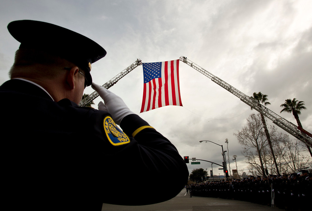 . A San Jose Police officer salutes there American Flag on Thursday outside of the HP Pavilion after the memorial service for detective Sgt. Loran \'Butch\' Baker and detective Elizabeth Butler.(Kevin Johnson/Sentinel)