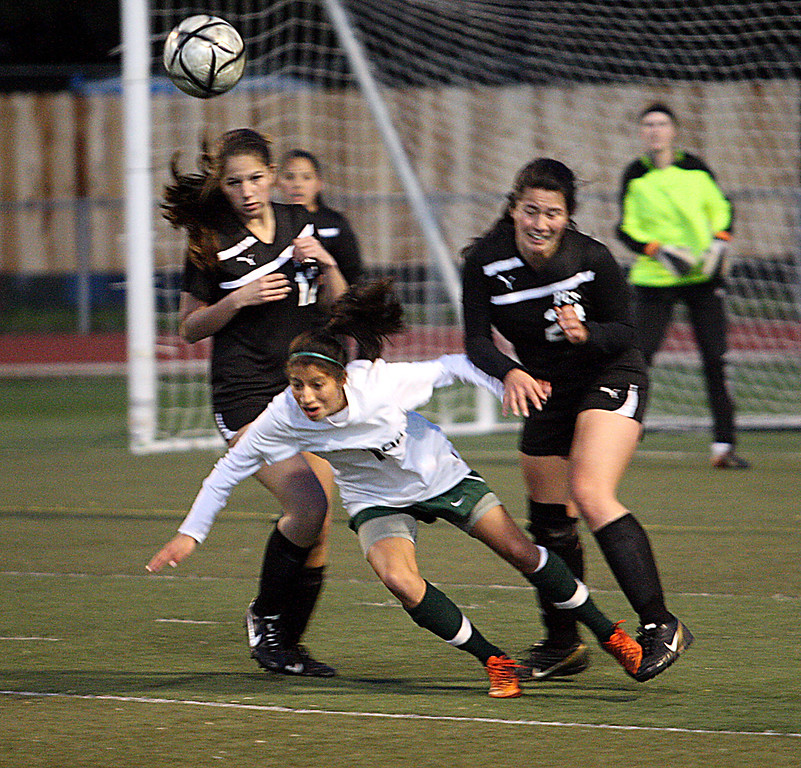 . Pacific Collegiate defenders Katre Binger and Takemi Kawamoto send Harbor High\'s Jessie Tobon flying in front of the PCS goal during their Central Coast Section D-III girls soccer match Wednesday, Feb. 20, 2013, at Soquel High in Soquel, Calif. Harbor won 2-0. (Dan Coyro/Sentinel)