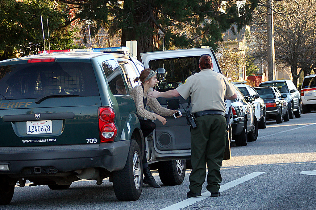 . Sheriff\'s deputy brings a woman wearing a black apron to the command center to provide information to law enforcement personnel Tuesday after two Santa Cruz Police detectives were shot and later died along with the suspect.  (Dan Coyro/Sentinel)