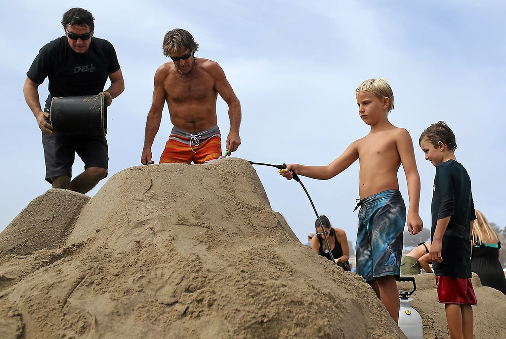 . Nine-year-old Jake Wickman, second from right, Doug Heath, center, and Nate Downs build an elaborate sand castle at Capitola Beach on Saturday during the annual sand castle competition. (Kevin Johnson -- Santa Cruz Sentinel)