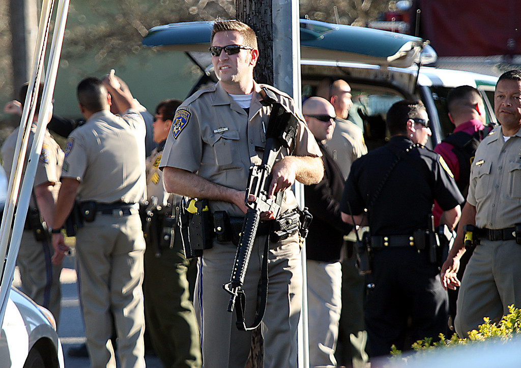 . A CHP officer carries his rifle at the shooting scene near N. Branciforte Ave. and Water St. Tuesday.  (Dan Coyro/Sentinel)