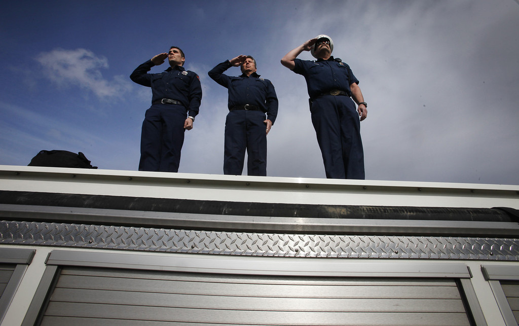 ". Santa Clara County firefighters, from left, Dave Sosine, Bruce Ingle and Capt. Dave Riggert, salute from atop their fire truck on the Bear Creek Rd. overpass as a procession of police officers from supporting agencies, coming from Santa Cruz heads north on Highway 17 on their way to HP Pavilion in San Jose Thursday, March 7, 2013. The procession was to the memorial service for Santa Cruz city police officers Loran ""Butch\"" Baker and Elizabeth Butler, shot to death on Feb. 26 when they followed up on a sexual assault investigation with an unstable man with a history of sexual assault. The gunman, Jeremy Goulet, was killed moments later by responding Santa Cruz County sheriff\'s deputies.  (Patrick Tehan/Staff)"
