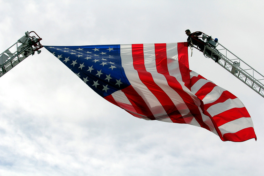 . A San Jose firefighter adjusts a large flag flying over Santa Clara Street for Thursday\'s memorial. (Shmuel Thaler/Sentinel)