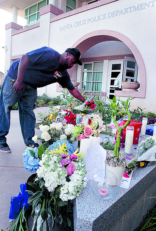 . Passerby William Elmore lays a bouquet of flowers at the memorial to detectives Elizabeth Butler and Loran \'Butch\' Baker at Santa Cruz Police Headquarters Wednesday morning. (Shmuel Thaler/Sentinel)