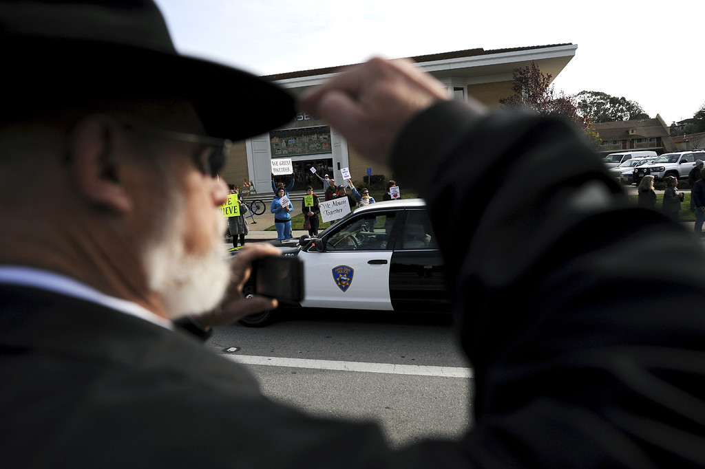 . A man stands at attention as the funeral procession for detectives Sgt. Loran \'Butch\' Baker and Elizabeth Butler moves down Ocean Street toward Highway 17 en route to HP Pavilion in San Jose, Calif., for memorial services. (Matthew Hintz/Sentinel).