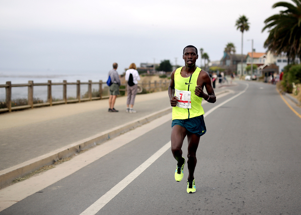 . Wharf to Wharf winner Simon Ndirangu charges towards the finish line in Capitola on Sunday. (Kevin Johnson -- Santa Cruz Sentinel)
