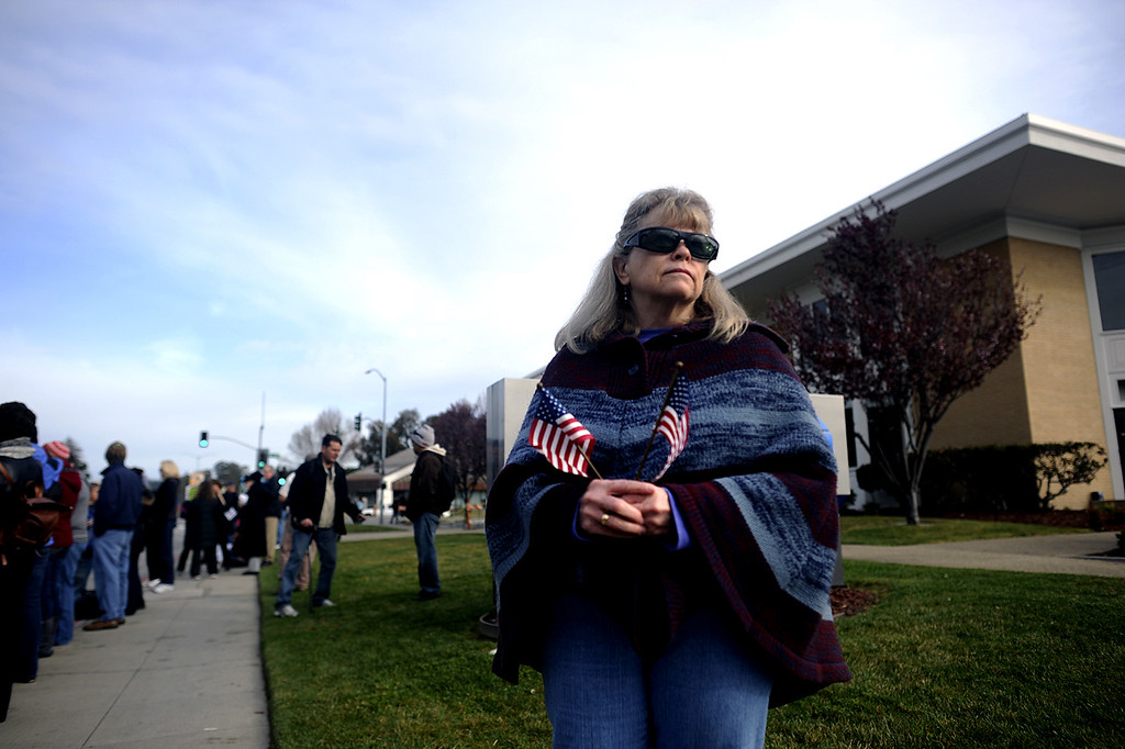 . Mary Oldem gathers with hundreds of others on the corner of Ocean Street and Water Street in Santa Cruz to watch the funeral procession en route to HP Pavilion in San Jose, Calif., for the memorial services for detectives Sgt. Loran \'Butch\' Baker and Elizabeth Butler (Matthew Hintz/Sentinel).