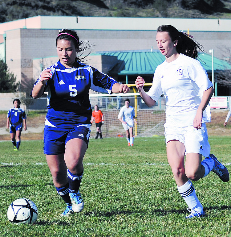 . The King\'s Academy\'s Katie Necas moves the ball down field with Scotts Valley\'s Mikaela Inman in pursuit in their first-round Central Coast Section Division III girls soccer game on Feb. 20, 2013. The King\'s Academy won 1-0. (Matthew Hintz/Sentinel).