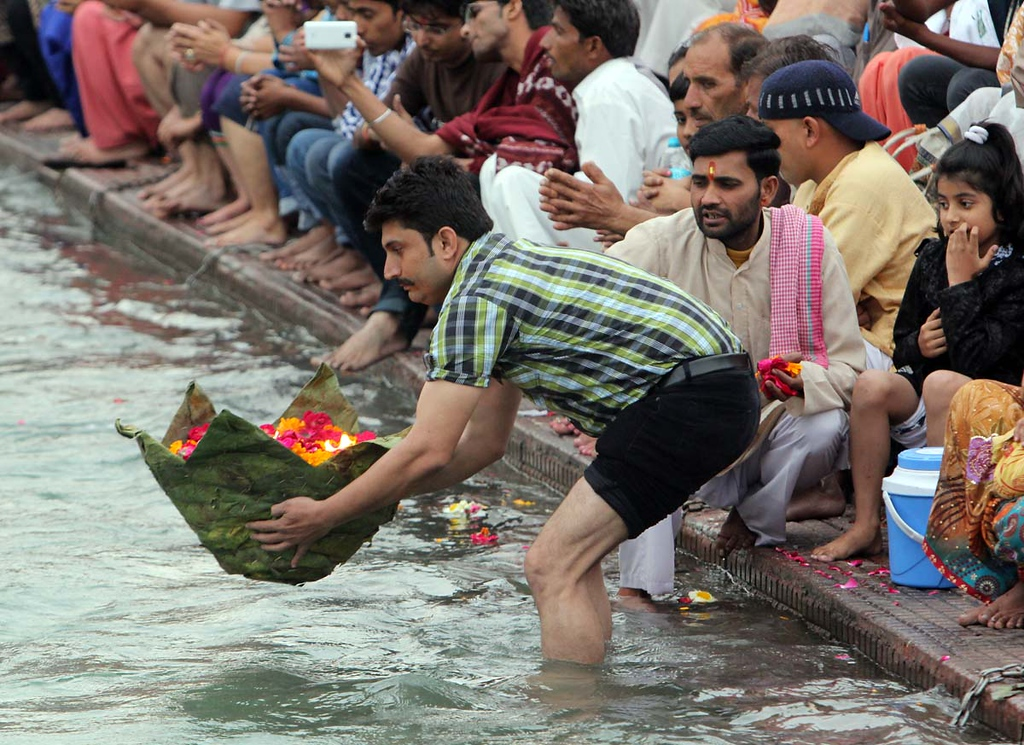 . A man places a large offering into the Ganges at Aarti  in Haridwar, India. Photos by Shmuel Thaler/Santa Cruz Sentinel