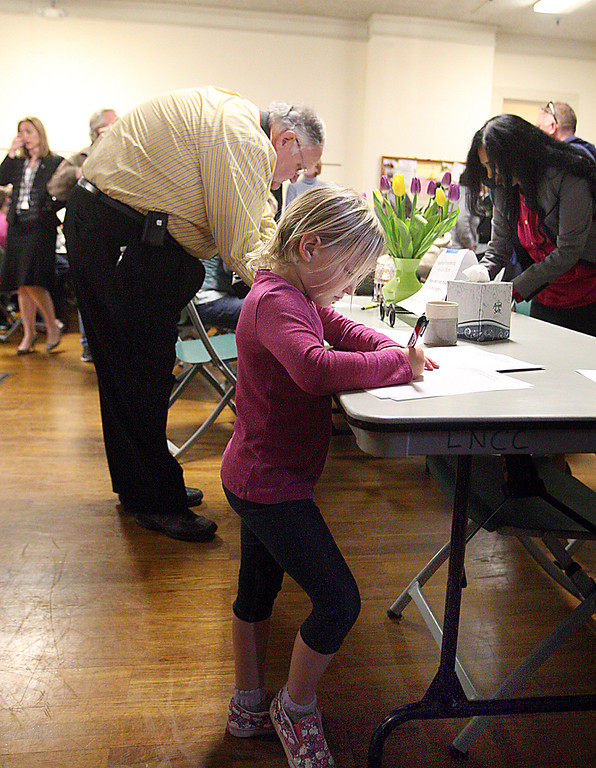 . Lucy Crumpton of Santa Cruz pens a note of condolence to the families of slain Santa Cruz Police detectives Loran \'Butch\' Baker and Elizabeth Butler KWednesday evening at the Louden Nelson Community Center.  (Dan Coyro/Sentinel)
