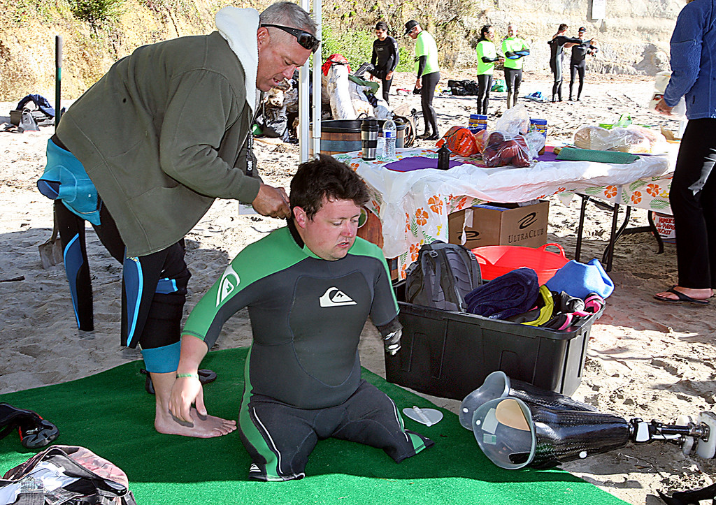 . Santa Cruz surfer Brent Edwards zips up the wetsuit of British soldier Martin Pollock Tuesday, April 16, 2013, at Cowell Beach as Operation Surf links up rehabbing wounded soldiers with surfers this week at the Cowell surf break in Santa Cruz, Calif.  (Dan Coyro/Sentinel)