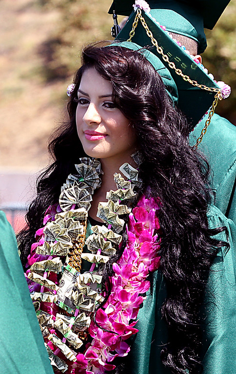 . Lizette Salgado sports a cash necklace as she marches into to her Pajaro Valley High graduation ceremony Thursday.  (Dan Coyro/Sentinel)