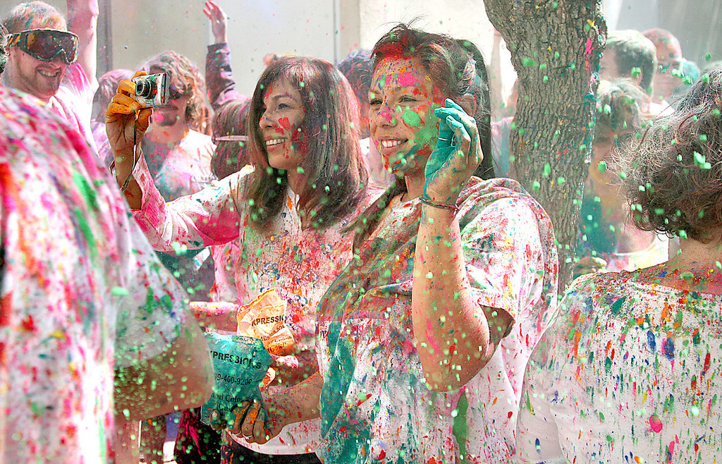 ". Participants of the Hindu festival ""Holi\"" celebrate the arrival of spring by throwing handfuls of colored powder at the Museum of Art and History Saturday, March 30, 2013."