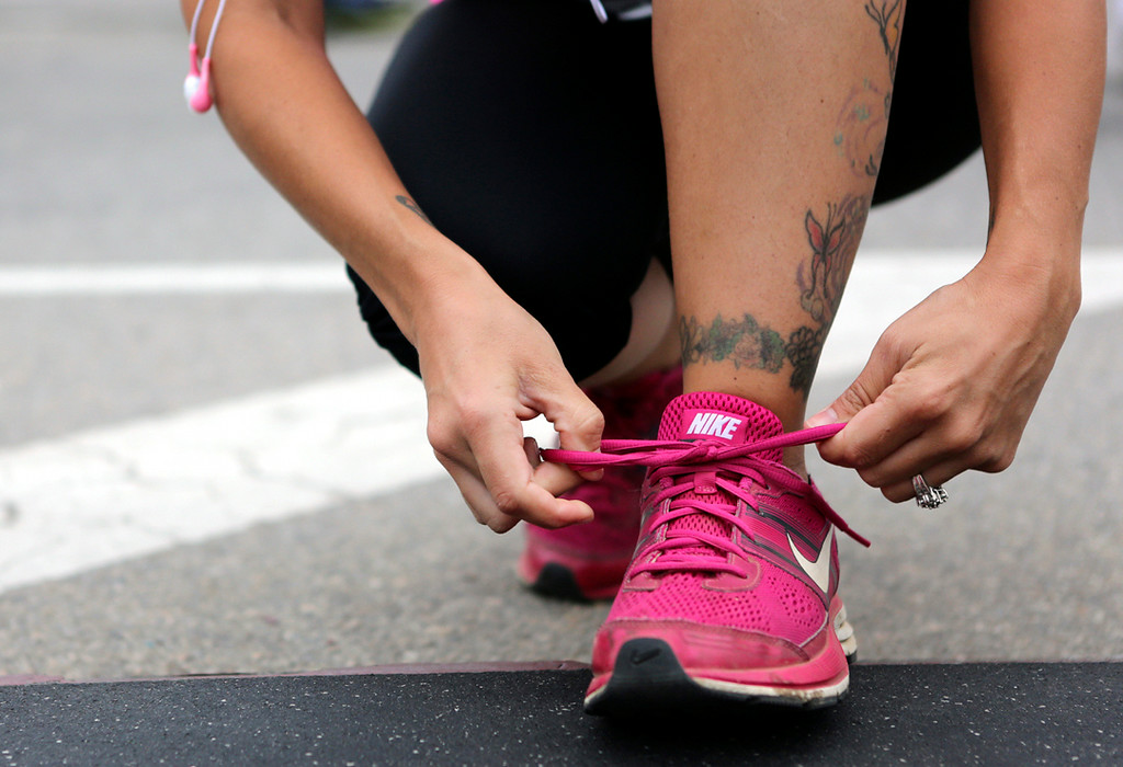 . A woman ties her bright-pink running shoes at the starting area of the 42nd annual Wharf to Wharf race on Beach Street in Santa Cruz on Sunday. (Kevin Johnson -- Santa Cruz Sentinel)