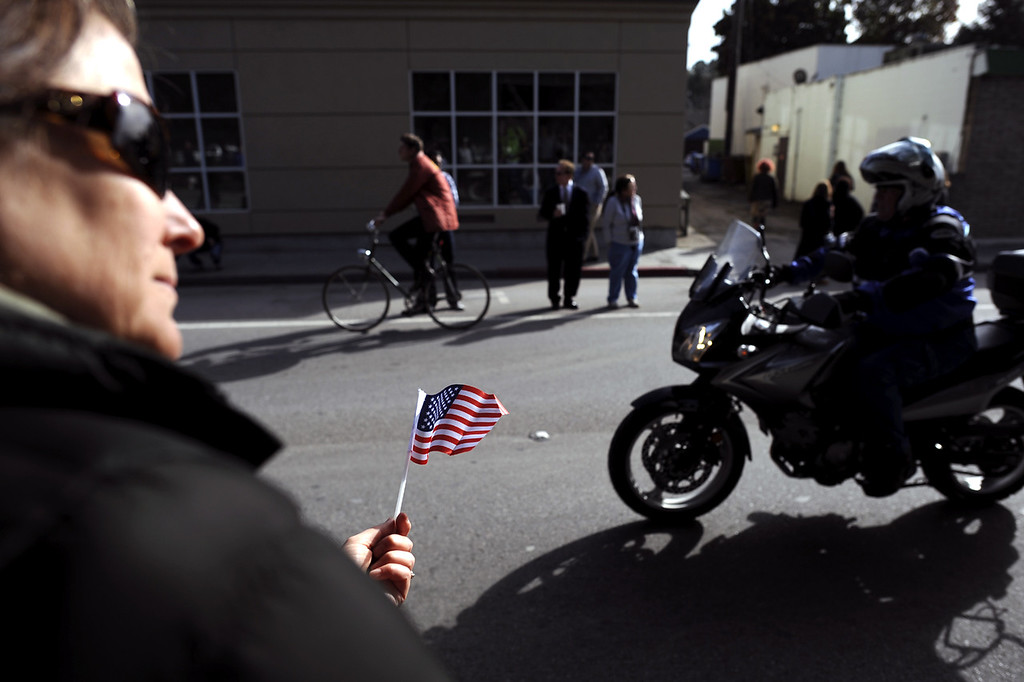 . A woman holding a flag looks down Ocean Street as the funeral procession for detectives Sgt. Loran \'Butch\' Baker and Elizabeth Butler approaches the corner of Ocean and Water Streets in Santa Cruz, Calif. The procession led to memorial services for the officers at HP Pavilion in San Jose. (Matthew Hintz/Sentinel).