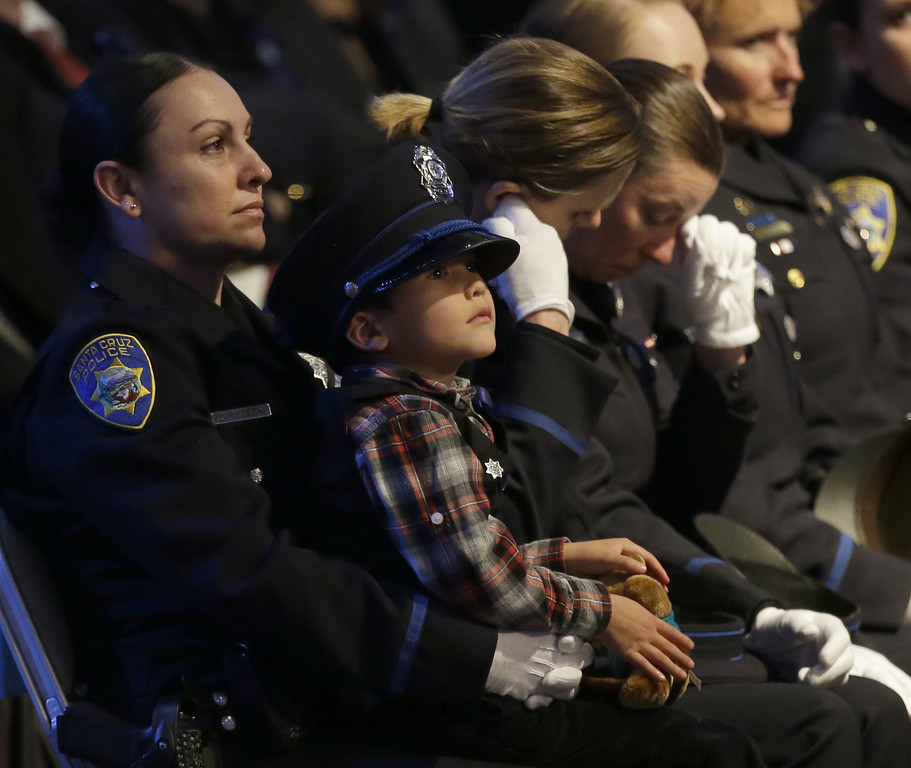 . Joaquin Wu, 5, sits on the lap of a Santa Cruz police officer as they attend a memorial service for Wu\'s mother, slain Santa Cruz police detective Elizabeth Butler, Thursday, March 7, 2013, at HP Pavilion  in San Jose, Calif. Sgt. Loran Baker and Detective Butler were shot to death on Feb. 27, after arriving at the home of Jeremy Peter Goulet to question him about a misdemeanor sexual assault. (AP Photo/Ben Margot)
