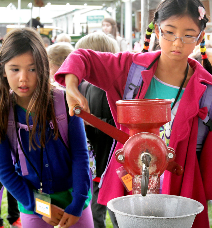 . Cassiopeia Tong grinds wheat berries the old fashioned way at Yesterday\'s Farm as her Delaveaga Elementary School third grade classmate Mina Hardwick waits her turn Wednesday. (Shmuel Thaler/Sentinel)