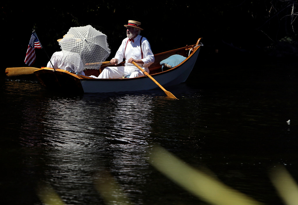 . White-clad boaters row along Soquel Creek in Capitola on Sunday during the annual Begonia Festival. (Kevin Johnson -- Santa Cruz Sentinel)