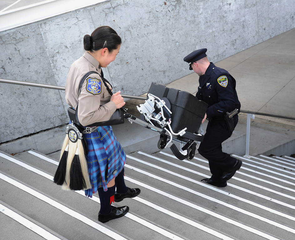 . San Rafael police officer David Casalnuovo, right, (cq) helps a member of the Santa Clara County Sheriffs Pipes and Drums Corp at the HP Pavilion in San Jose, Calif. on Thursday, March 7, 2013. Thousands are expected at the pavilion to mourn the loss of the two Santa Cruz police officers who lost their their lives in the line of duty last Tuesday. (Dan Honda/Staff)