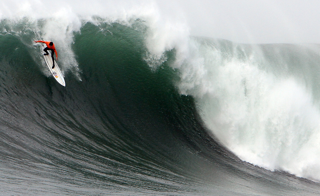 """. Grant \""""Twiggy\"""" Baker begins his descent on the face of a colossal wave during the final heat of the Mavericks Invitational surfing competition at Half Moon Bay on Friday.  (Kevin Johnson/Sentinel)"""