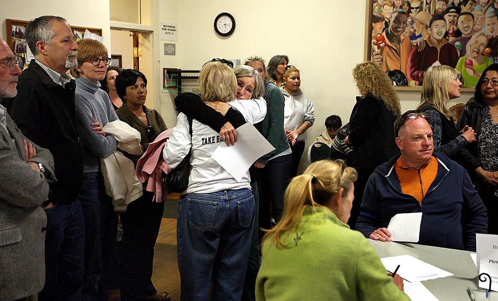 . Santa Cruz City Councilwoman Lynn Robinson hugs a member of Take Back Santa Cruz during a vigil for slain Santa Cruz Police detectives Loran \'Butch\' Baker and Elizabeth Butler Wednesday evening at the Louden Nelson Community Center.  (Dan Coyro/Sentinel)