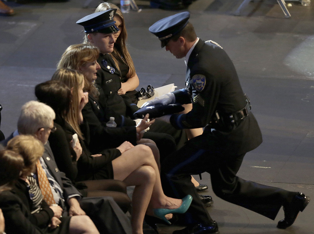 . The Baker family is presented a U.S. flag during a memorial service for slain Santa Cruz police Sgt. Loran Baker and detective Elizabeth Butler Thursday, March 7, 2013, at HP Pavilion  in San Jose, Calif. Baker and Butler were shot to death on Feb. 27, after arriving at the home of Jeremy Peter Goulet to question him about a misdemeanor sexual assault. (AP Photo/Ben Margot)