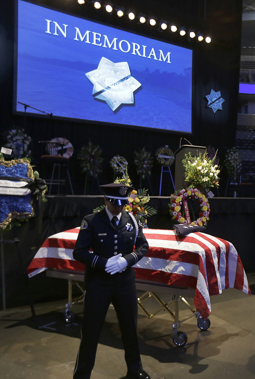. A policeman guards one of the caskets of slain Santa Cruz police Sgt. Loran Baker and detective Elizabeth Butler as they lie at a memorial service Thursday, March 7, 2013, at HP Pavilion  in San Jose, Calif. Baker and Butler were shot to death on Feb. 27, after arriving at the home of Jeremy Peter Goulet to question him about a misdemeanor sexual assault. (AP Photo/Ben Margot)