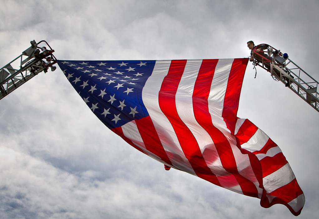 . An officer climbs a firetruck ladder to adjust a large American Flag having over the thousands of supporters that gathered at the HP Pavilion on Thursday. (Kevin Johnson/Sentinel)
