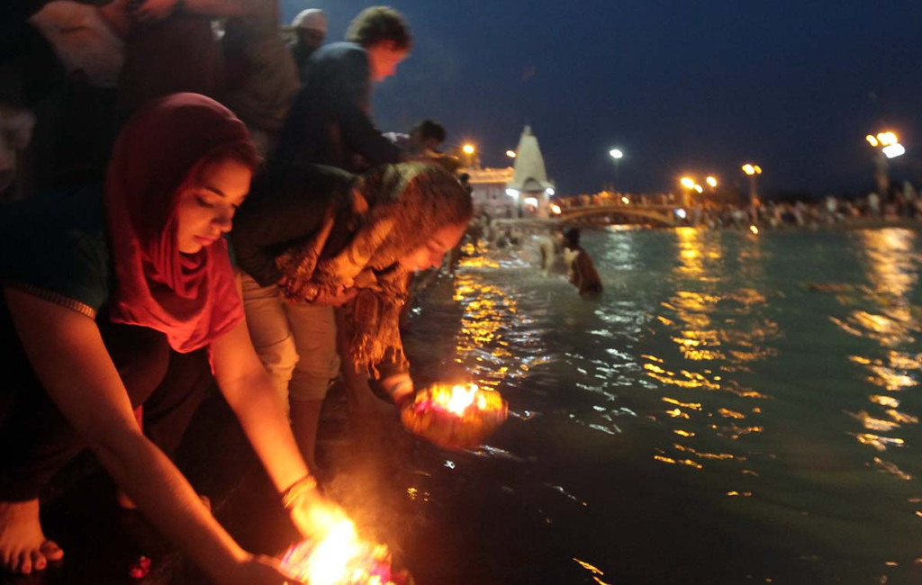 . Mount Madonna seniors Karina Fox , of Soquel, and Aimee Hopkins, of Corralitos, place memorial offerings into the Ganges River during Aarti at Haridwar, India on Friday. Photos by Shmuel Thaler/Santa Cruz Sentinel