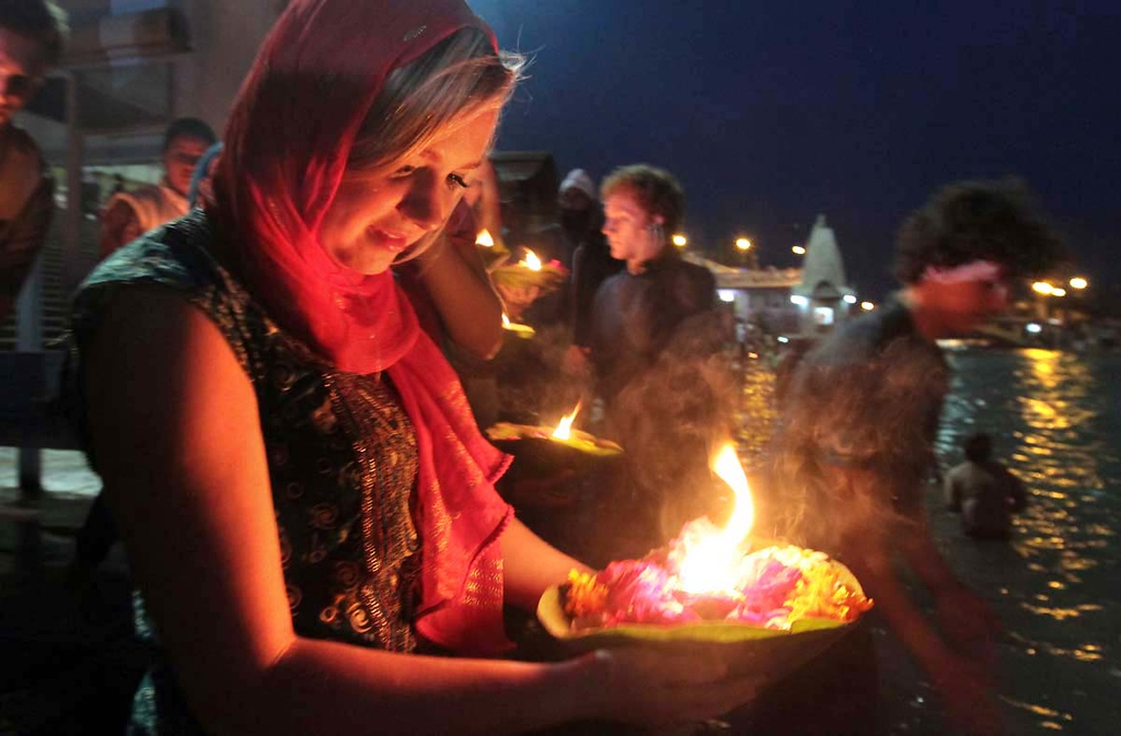 . Amber Zeise, of Capitola, carries an offering to the Ganges River at Hari Kapari, in Haridwar, India during Aarti on Friday as her Mount Madonna School classmates Joseph Frediani and Jake Getz also participate in the ritual. Photos by Shmuel Thaler/Santa Cruz Sentinel