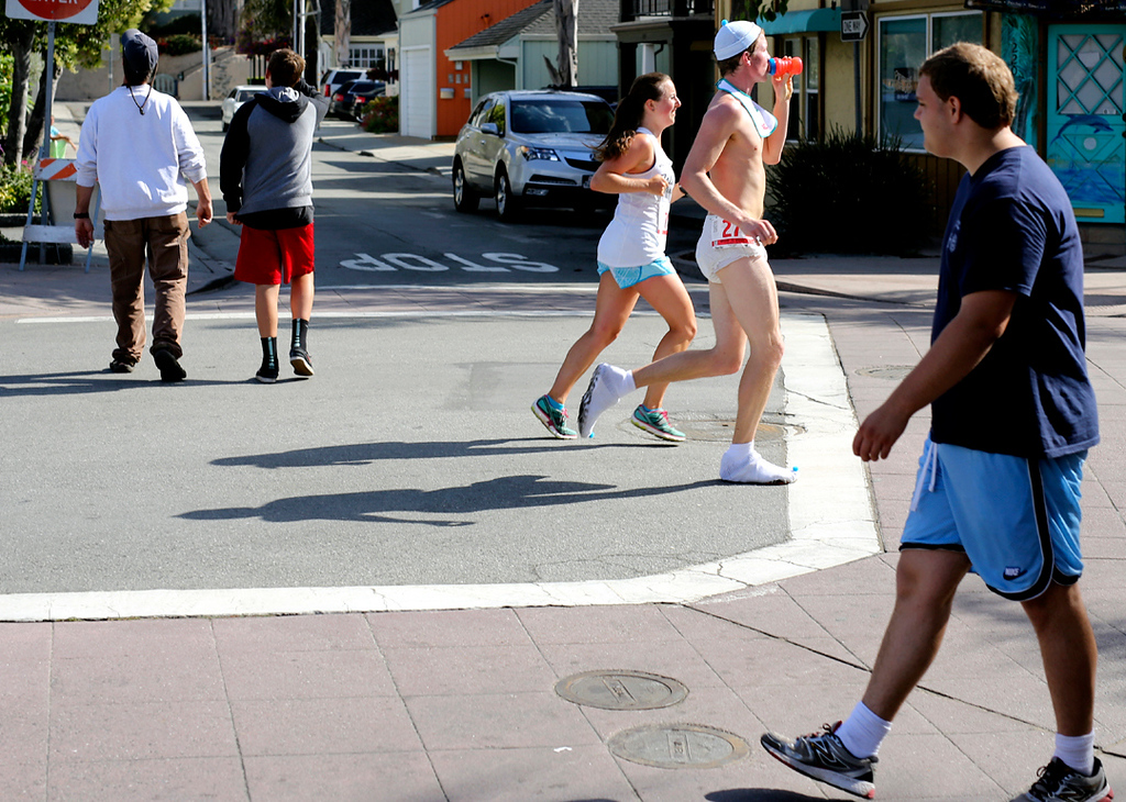 . A man dressed as a giant baby sips from his water bottle as he runs through Capitola Village on Sunday after the Wharf to Wharf race. (Kevin Johnson -- Santa Cruz Sentinel)