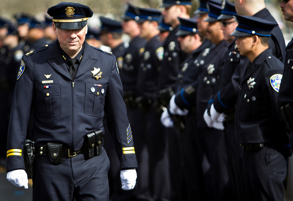 . Santa Cruz Police Deputy Chief Rick Martinez walks between two rows of SCPD officers on Thursday outside of the HP Pavilion in San Jose before the memorial service for detective Sgt. Loran \'Butch\' Baker and detective Elizabeth Butler. (Kevin Johnson/Sentinel)
