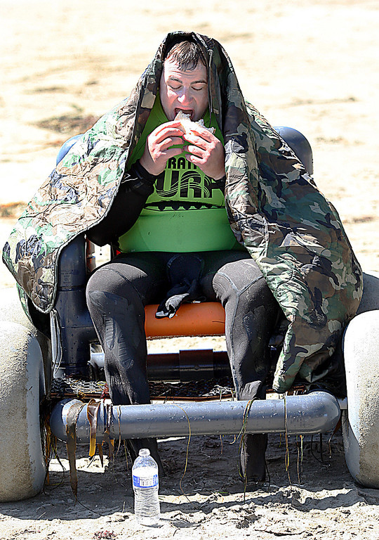 . Ryan Hawk of San Antonio warms up while eating a sandwich after a morning surf session at Cowell Beach in Santa Cruz, Calif., Tuesday, April 16, 2013.  (Dan Coyro/Sentinel)