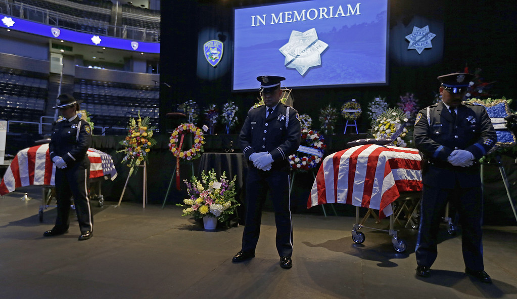 . Police stand guard over the caskets of slain Santa Cruz police Sgt. Loran Baker and detective Elizabeth Butler lie at a memorial service Thursday, March 7, 2013, at HP Pavilion  in San Jose, Calif. Baker and Butler were shot to death on Feb. 27, after arriving at the home of Jeremy Peter Goulet to question him about a misdemeanor sexual assault. (AP Photo/Ben Margot)