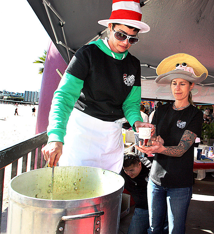 . Adele Gemignani and Randy Williams serve up some Dr. Suess-style green clam chowder at their Clam-I-Am team booth at the Boardwalk\'s 32nd annual Clam Chowder Cook-Off in Santa Cruz, Calif., on Saturday, Feb. 23, 2013. (Dan Coyro/Sentinel)