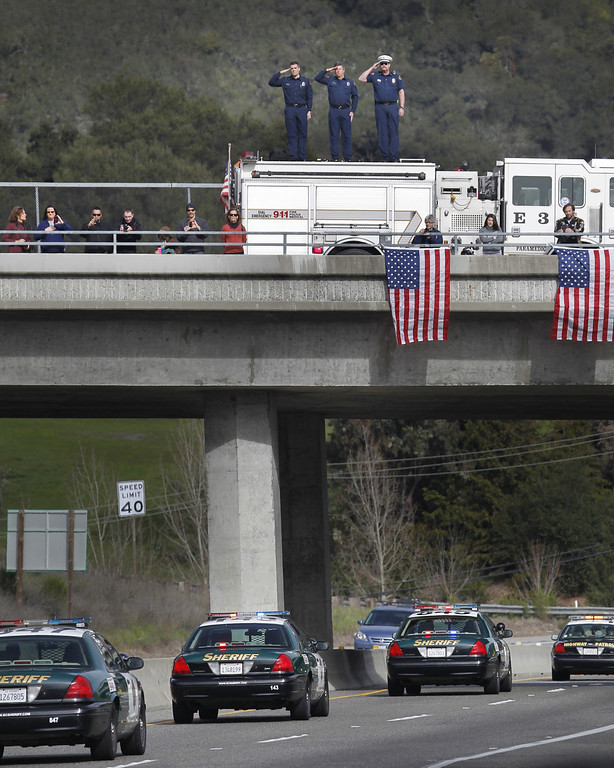 ". Santa Clara County firefighters, from left, Dave Sosine, Bruce Ingle and Capt. Dave Riggert, salute from atop their fire truck on the Bear Creek Rd. overpass as a procession of police officers from supporting agencies, coming from Santa Cruz heads north on Highway 17 on their way to HP Pavilion in San Jose, California, Thursday, March 7, 2013. The procession was to the memorial service for Santa Cruz city police officers Loran ""Butch\"" Baker and Elizabeth Butler. (Patrick Tehan/San Jose Mercury News/MCT)"