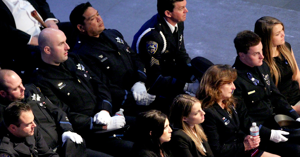 . Santa Cruz police detective Sgt. Loran \'Butch\' Baker\'s widow Kelly, third from right, is flanked by their daughter Jillian and son Adam during Baker\'s memorial service at HP Pavilion Thursday. (Shmuel Thaler/Sentinel)