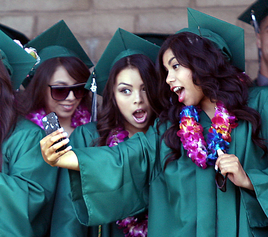 . Pajaro Valley High grads snap phone photos before marching into their graduation ceremony Thursday at Cabrillo College.  (Dan Coyro/Sentinel)