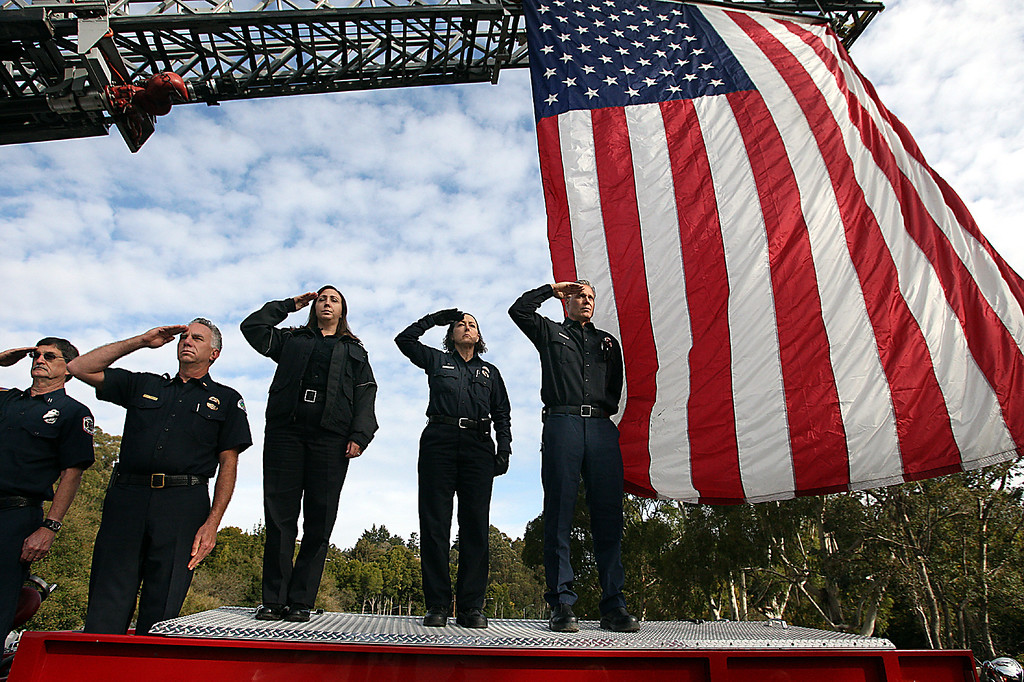 . Firefighters standing atop an engine parked on the Pasatiempo Highway 17 overpass salute the passing funeral procession of slain Santa Cruz Police detectives Sgt. Loran \'Butch\' Baker and Elizabeth Butler on Thursday.  Memorial services were at HP Pavilion in San Jose, Calif. (Dan Coyro/Sentinel)