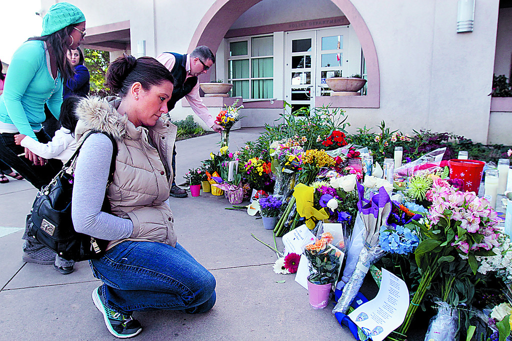 . Passersby spend some time at the memorial in front of the Santa Cruz Police Department Wednesday. (Shmuel Thaler/Sentinel)